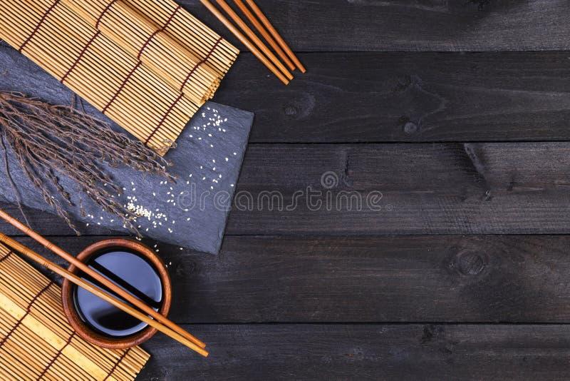 Fondo per i sushi Salsa di bambù di soia e della stuoia sulla tavola di legno nera Vista superiore con lo spazio della copia fotografia stock libera da diritti