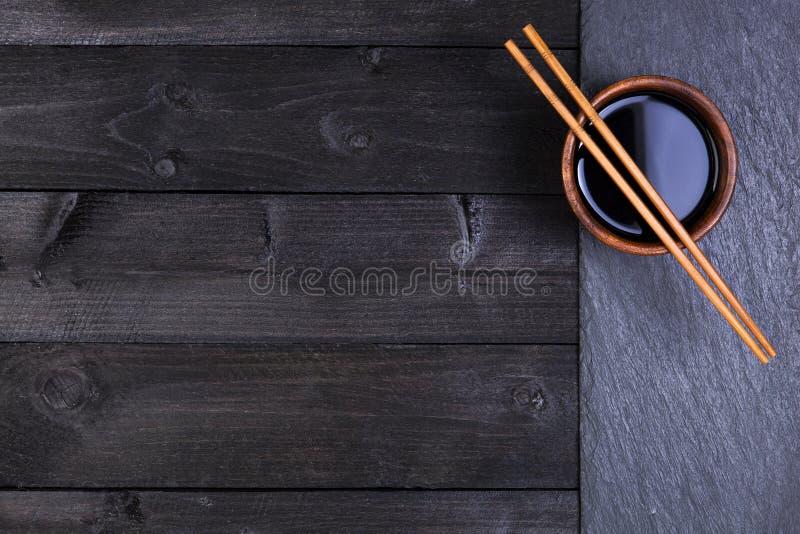 Fondo per i sushi Salsa di soia, bastoncini sulla pietra nera Vista superiore con lo spazio della copia fotografia stock libera da diritti