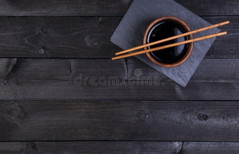Fondo per i sushi Salsa di soia, bastoncini sulla pietra nera Vista superiore con lo spazio della copia immagine stock libera da diritti