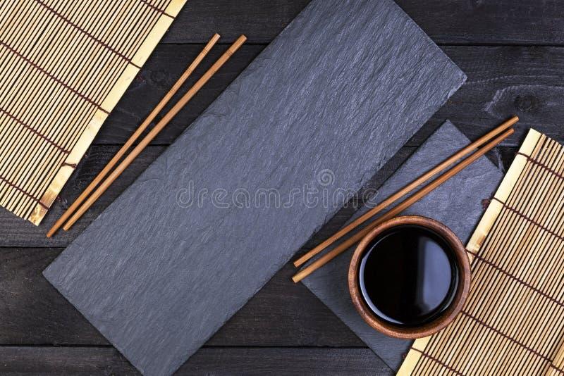 Fondo per i sushi Stuoia di bambù, salsa di soia, bastoncini sulla tavola scura fotografia stock