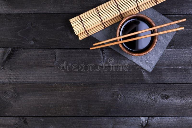 Fondo per i sushi Stuoia di bambù, salsa di soia, bastoncini sulla tavola scura immagine stock