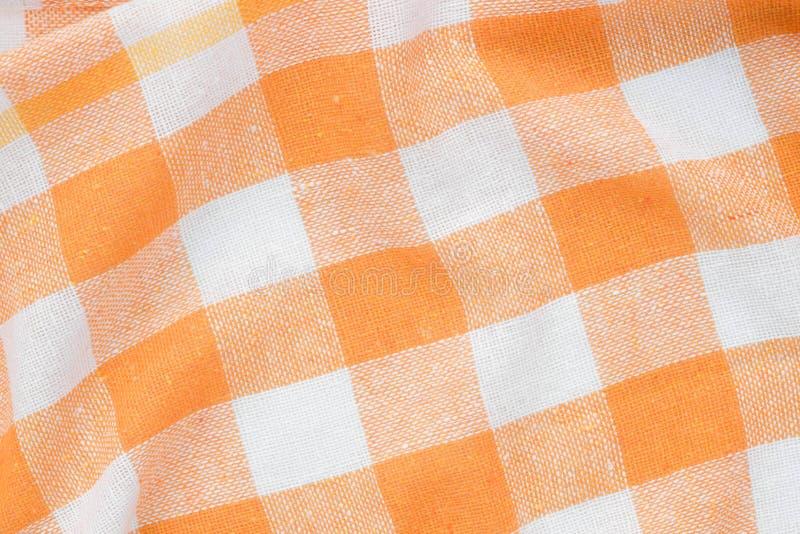 Fondo piegato a quadretti arancio e bianco dell'asciugamano di cucina fotografie stock libere da diritti