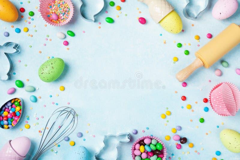 Fondo que cuece de Pascua con el rodillo, el batidor, los huevos decorativos, los cortadores de la galleta, el caramelo y el conf imagen de archivo