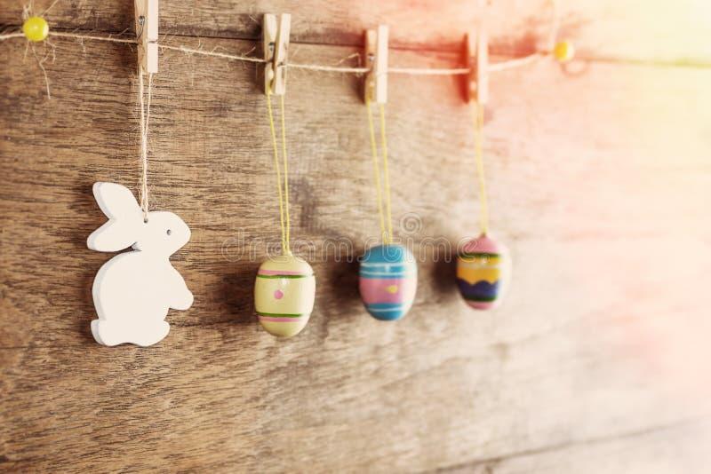 Fondo rústico de Pascua: Los huevos pintados vintage y el conejito blanco cuelgan en pinzas contra la pared de madera marrón viej foto de archivo libre de regalías