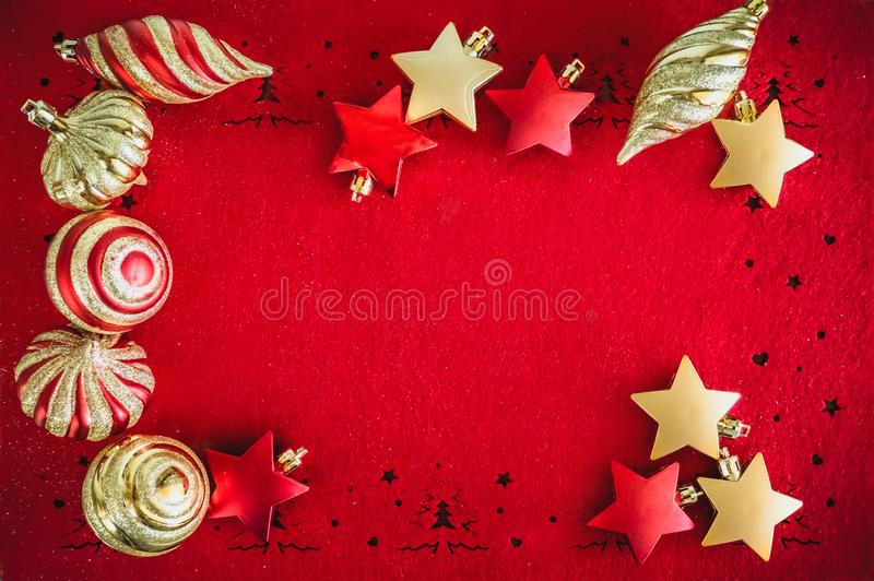 Fondo rojo de la tarjeta de Navidad con las decoraciones, bolas y estrellas, y espacio de oro para su texto foto de archivo