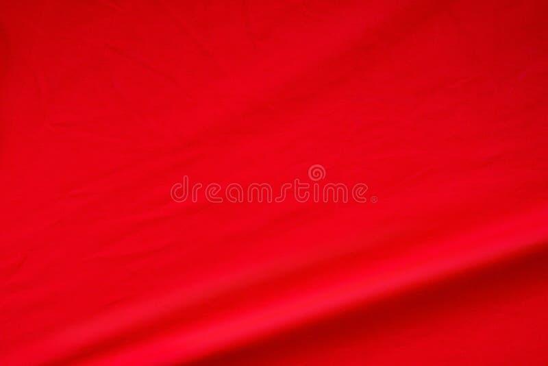 Fondo rojo de la tela Textura de seda viva elegante del material de la onda imagenes de archivo