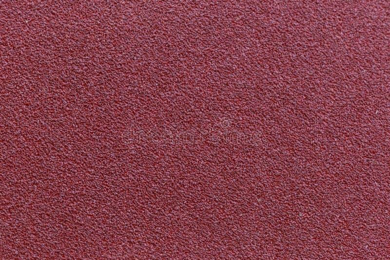 Fondo rojo de la textura del papel de lija para el diseño foto de archivo