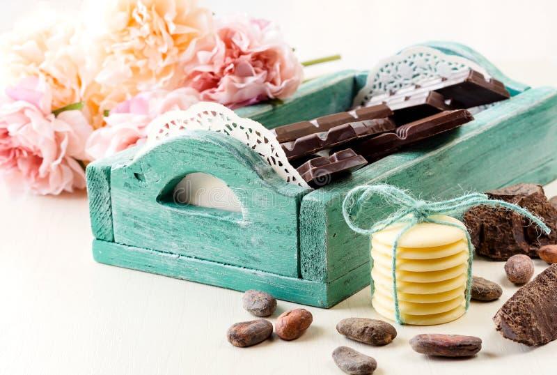 Fondo romántico con el chocolate negro en una caja de madera del vintage verde, los granos de cacao y los pedazos de chocolate d fotos de archivo libres de regalías