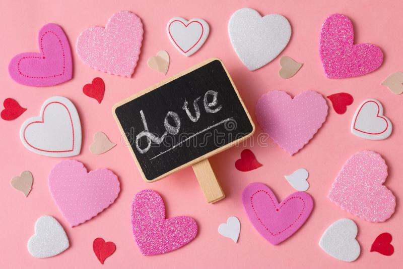 Fondo romántico del día de tarjetas del día de San Valentín Un gran número de corazones de diverso tamaño con poca pizarra y pala foto de archivo libre de regalías