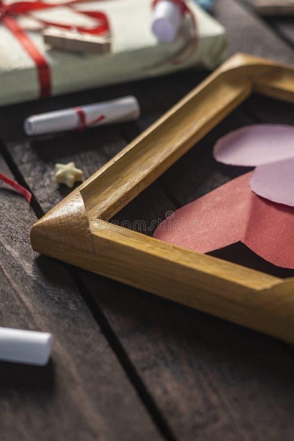 Fondo romantico posto piano Giftbox, carte rotolate di desiderio e struttura di legno con i cuori di carta sul bordo di legno scu fotografia stock