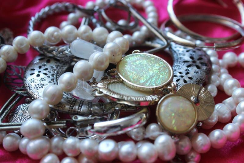 Fondo rosa con le perle bianche ed altri gioielli Bella struttura immagine stock