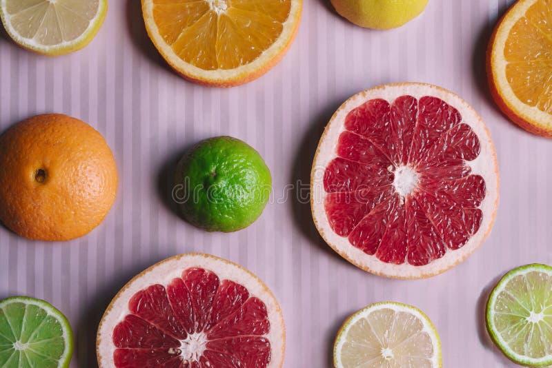 Fondo rosa a strisce con le fette dell'agrume: arancia, pompelmo, limone, umore del limeRainbow fotografie stock