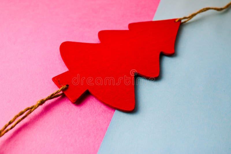 Fondo rosado azul alegre multicolor de la Navidad festiva del Año Nuevo con árbol de navidad lindo rojo del pequeño juguete y bla fotos de archivo