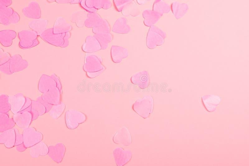 Fondo rosado con confeti en forma de corazón imagenes de archivo