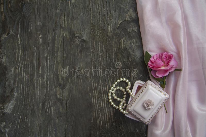 Fondo rosado con las gotas de una caja y de la perla imagen de archivo