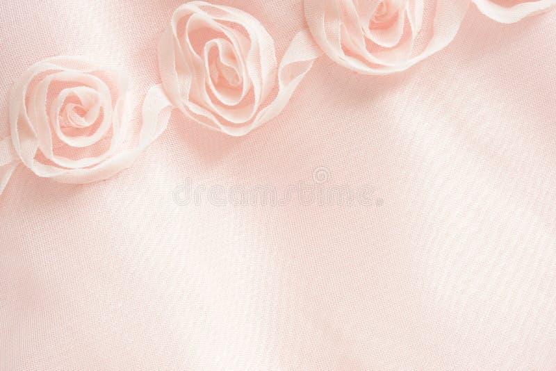 Fondo rosado de la materia textil con las rosas fotos de archivo
