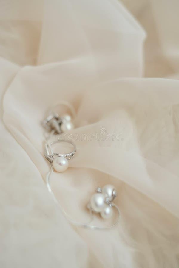 fondo rosado en colores pastel de la tela del fondo de la perla del anillo de bodas fotografía de archivo