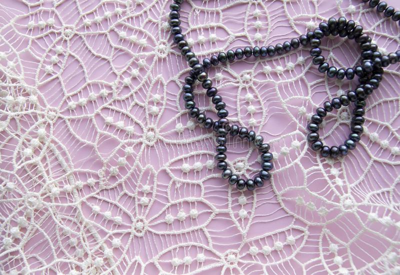 Fondo rosado plano de la endecha y el cordón magnífico, el collar que brilla de perlas negras, y la pulsera elegante Belleza y mo fotografía de archivo libre de regalías