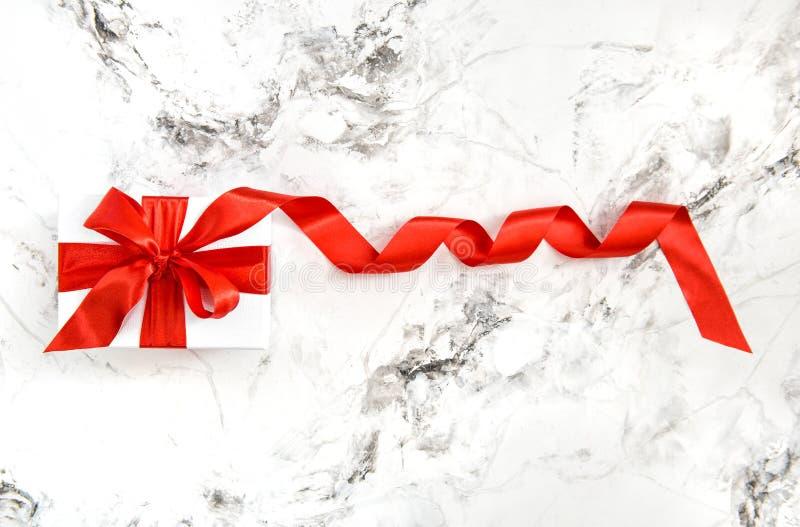 Fondo rosso bianco del marmo dell'arco del nastro del raso del contenitore di regalo fotografie stock