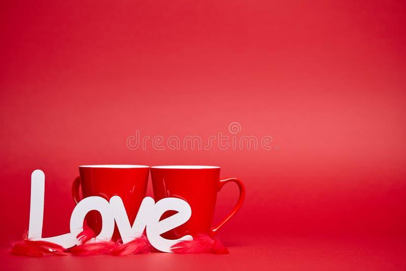 Fondo rosso con le tazze ed il segno di amore fotografie stock libere da diritti