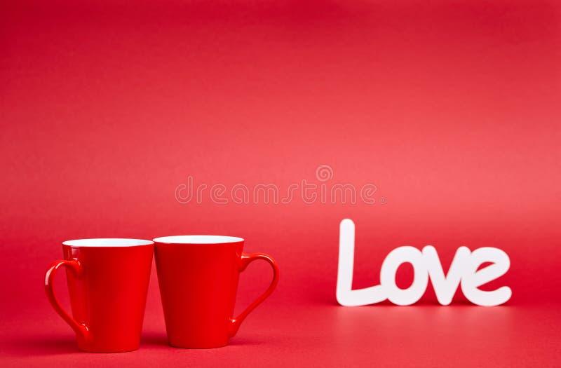 Fondo rosso con le tazze ed il segno di amore immagine stock