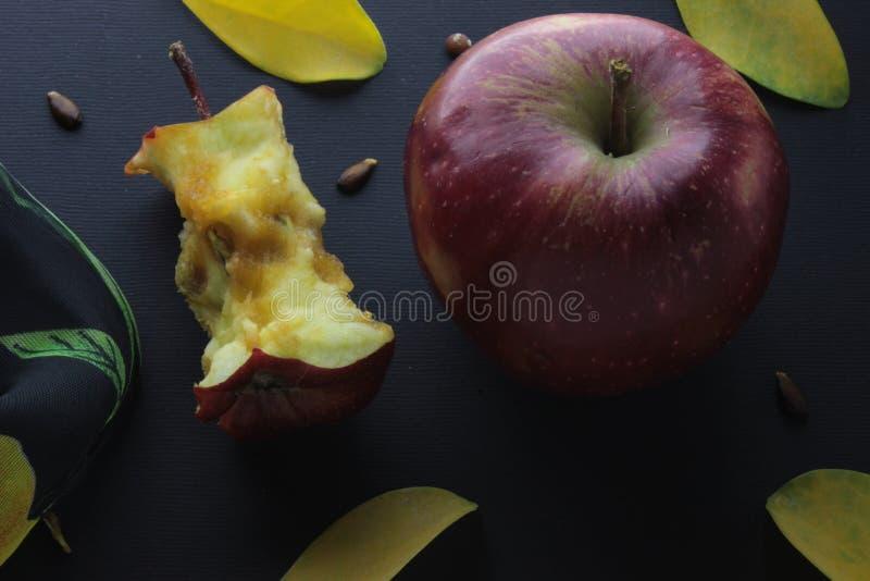 Fondo rosso della carta del mestiere di Stub Core Composition On Black del ceppo di Apple e di Apple fotografia stock