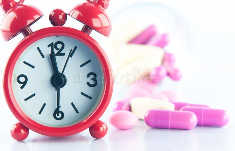 Fondo rosso della medicina e dell'orologio immagini stock