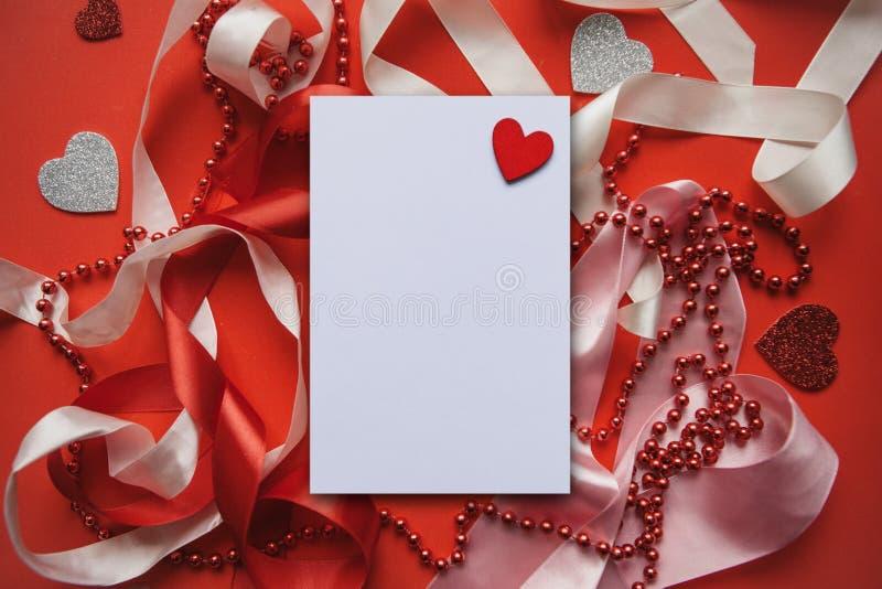 Fondo rosso festivo con i nastri, le perle ed i cuori immagini stock libere da diritti