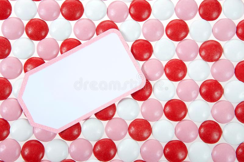Fondo rotondo rosso, di rosa e bianco della caramella con la carta in bianco sulla cima immagine stock libera da diritti