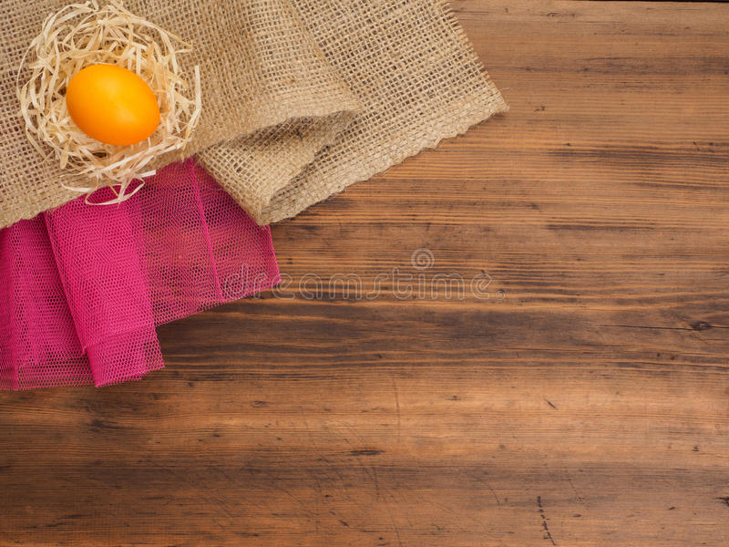 Fondo rural del eco con el huevo y la paja anaranjados del pollo en el fondo de la arpillera y de los tablones de madera viejos L imágenes de archivo libres de regalías
