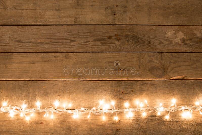 Fondo rustico di Natale - l'annata planked il legno con le luci e lo spazio del testo fotografia stock