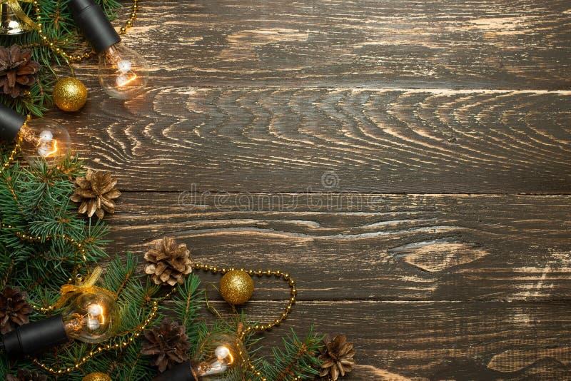 Fondo rustico di Natale - vecchio bordo di legno con la lampadina e rami di un albero di Natale e uno shyshkami e uno spazio del  immagine stock libera da diritti