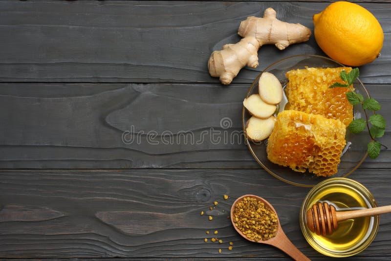 Fondo sano miele, favo, limone, tè, zenzero sulla tavola di legno scura Vista superiore con lo spazio della copia fotografia stock