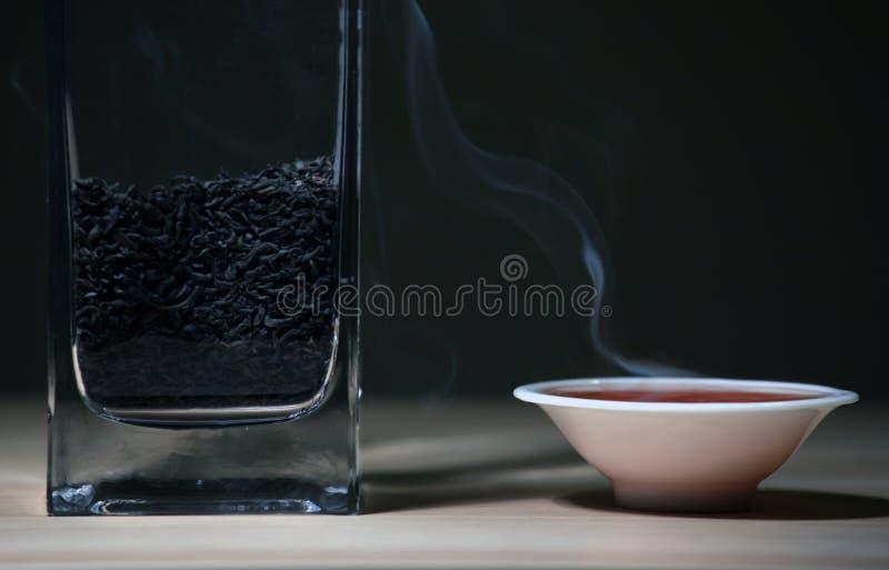 Fondo scuro di tè della tazza della tavola di legno cinese calda nera del fumo nessuno immagine stock