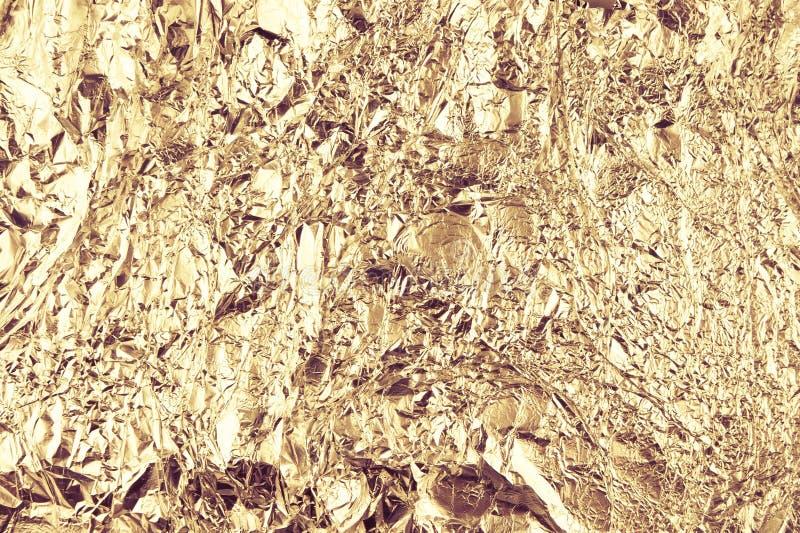 Fondo sgualcito astratto della stagnola Fondo della foto di lerciume Colori dell'oro fotografia stock