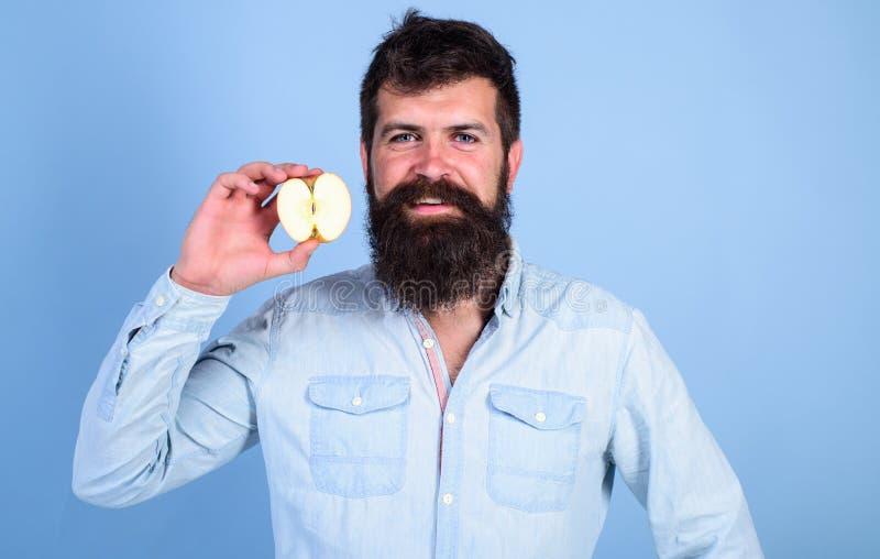 Fondo sonriente barbudo del azul de la manzana de los controles del hombre Mitad de la forma de vida sana de la manzana Concepto  imagen de archivo