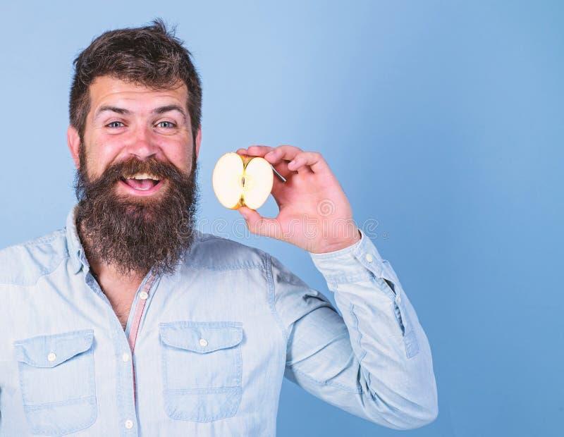 Fondo sonriente barbudo del azul de la manzana de los controles del hombre Mitad de la forma de vida sana de la manzana El inconf fotografía de archivo