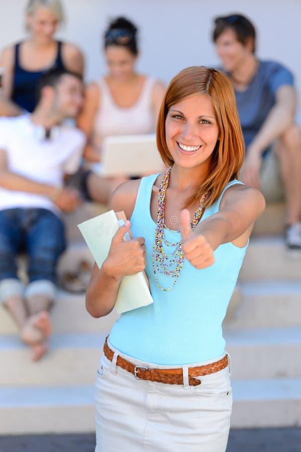 Fondo sonriente de los amigos del pulgar-para arriba de la muchacha del estudiante foto de archivo