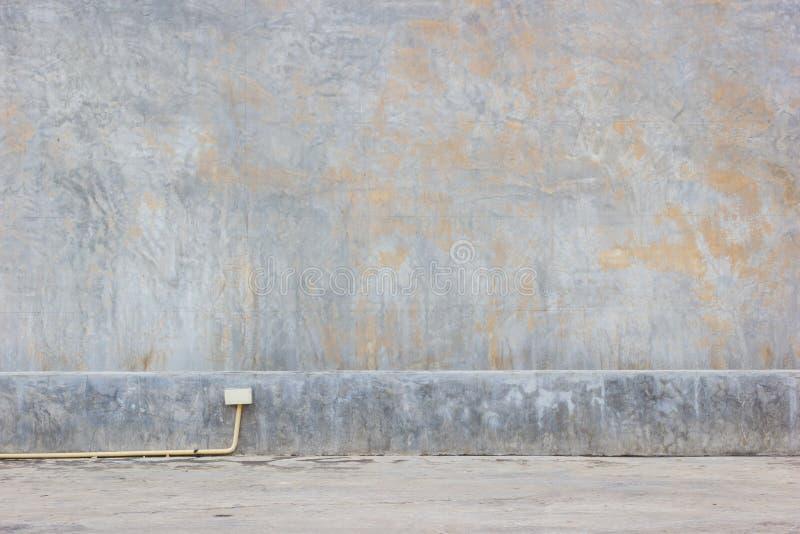 Fondo sporco del muro di cemento del fango Grungy con il tubo giallo o del PVC immagini stock