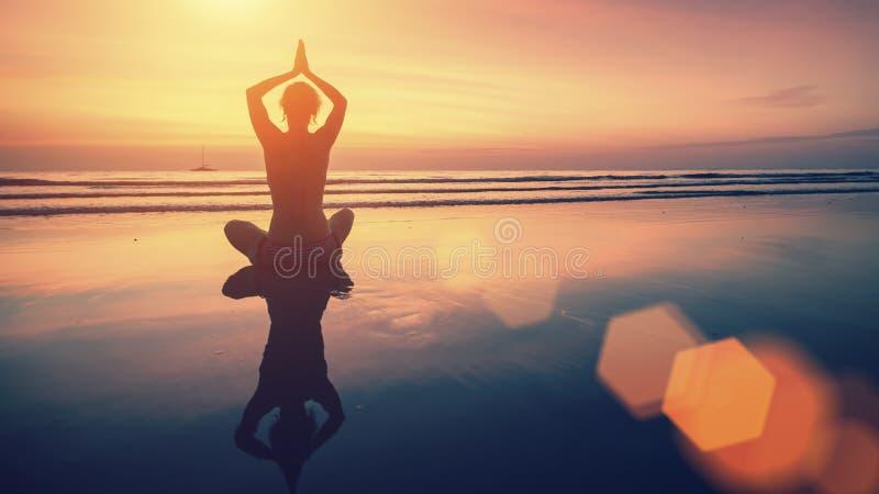Fondo stupefacente di yoga, siluetta della donna sulla spiaggia al bello tramonto fotografia stock