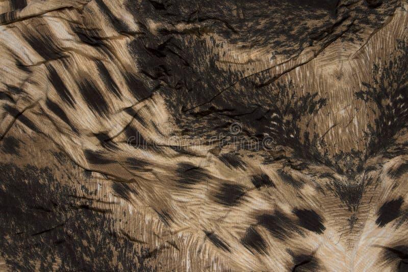 Fondo, textura de un fragmento de la tela retra con un estampado leopardo imagenes de archivo