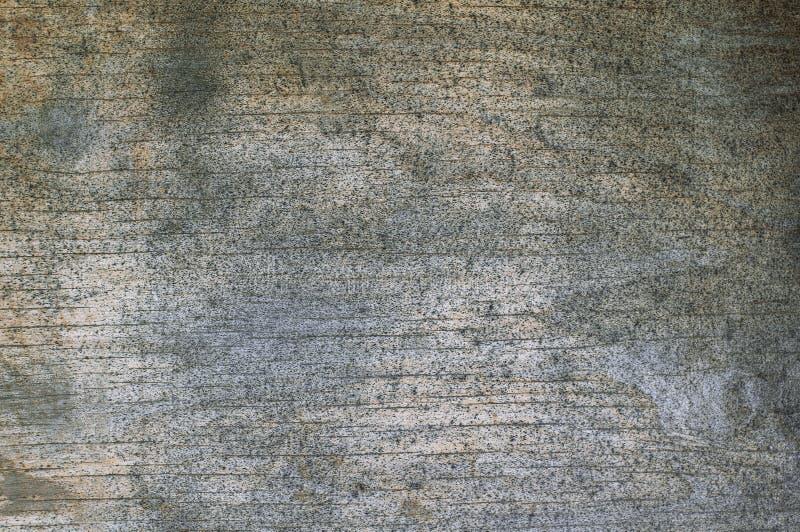 Fondo texturizado del tablero descolorado de la madera contrachapada que se cubre con los puntos y las grietas negros fotografía de archivo libre de regalías