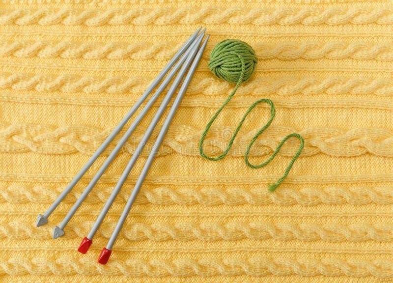 Fondo tricottato giallo con il modello e le trecce; Grey Knitting Needle e palla verde Fatto a mano fotografia stock