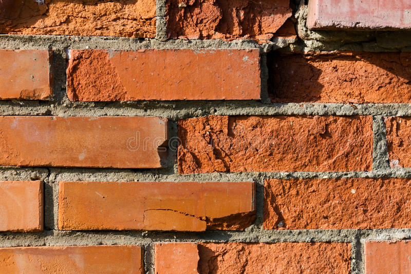 Fondo, una pared hecha de ladrillos rojos, desmenuzado parcialmente fotos de archivo libres de regalías
