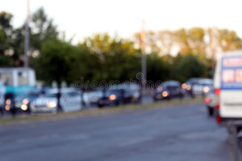 Fondo unfocused borroso con el camino urbano con transporte en la iluminaci?n de la puesta del sol Fuera de paisaje de la ciudad  imagen de archivo libre de regalías
