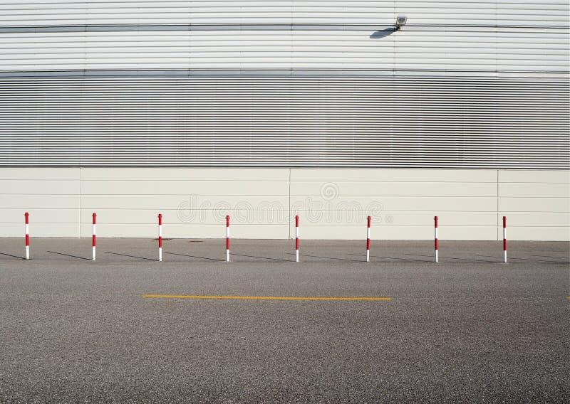 Fondo urbano de la calle Polos blancos y rojos del borde de la carretera en la carretera de asfalto delante de una pared blanca h foto de archivo libre de regalías