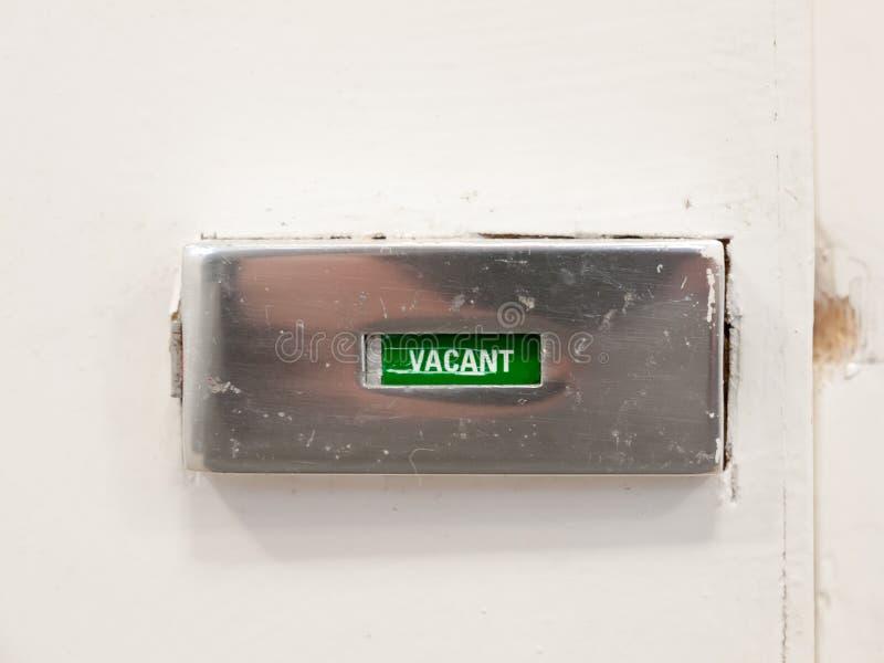 Fondo vacante del blanco del metal de la muestra del retrete del cuarto de baño de la puerta foto de archivo