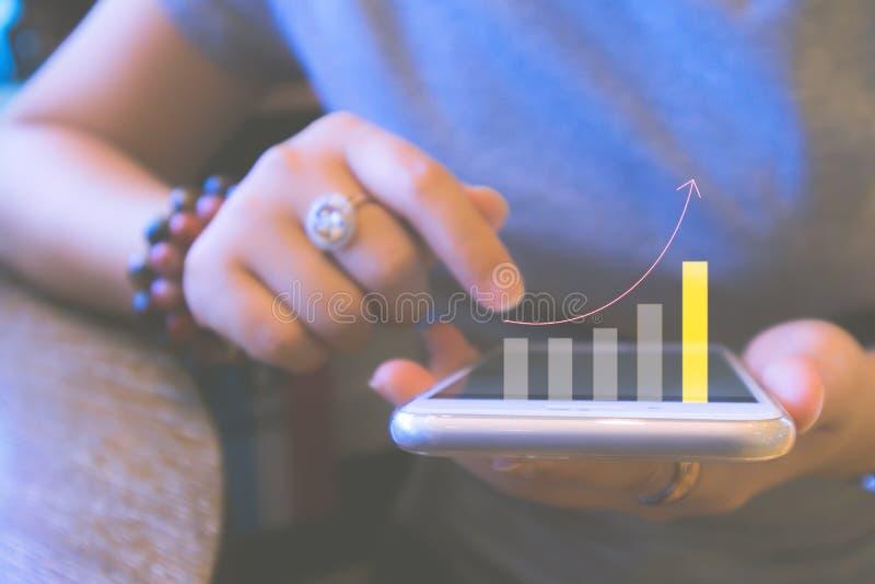 Fondo vago di pianificazione finanziaria e del concetto di investimento Smartphone della tenuta della giovane donna con il grafic immagini stock