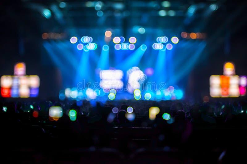 Fondo vago: Illuminazione di Bokeh di concerto con il pubblico, MU fotografia stock