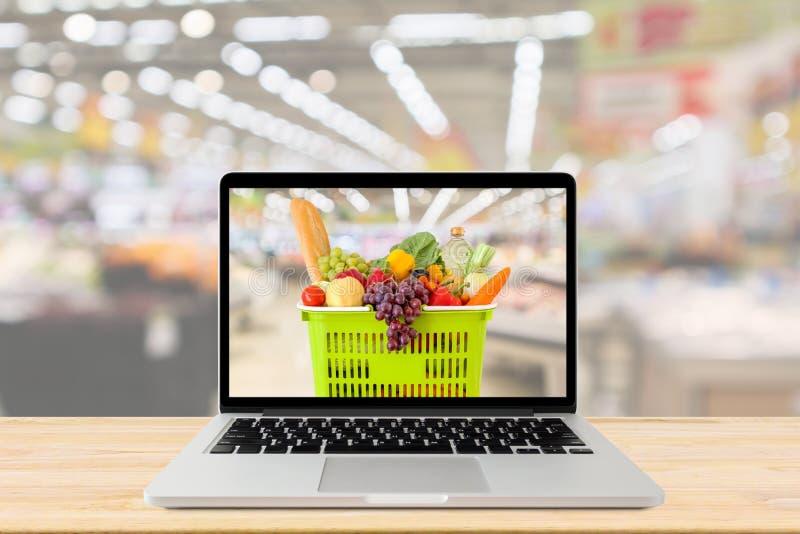 Fondo vago navata laterale del supermercato con il computer portatile ed il cestino della spesa sulla tavola di legno immagini stock libere da diritti
